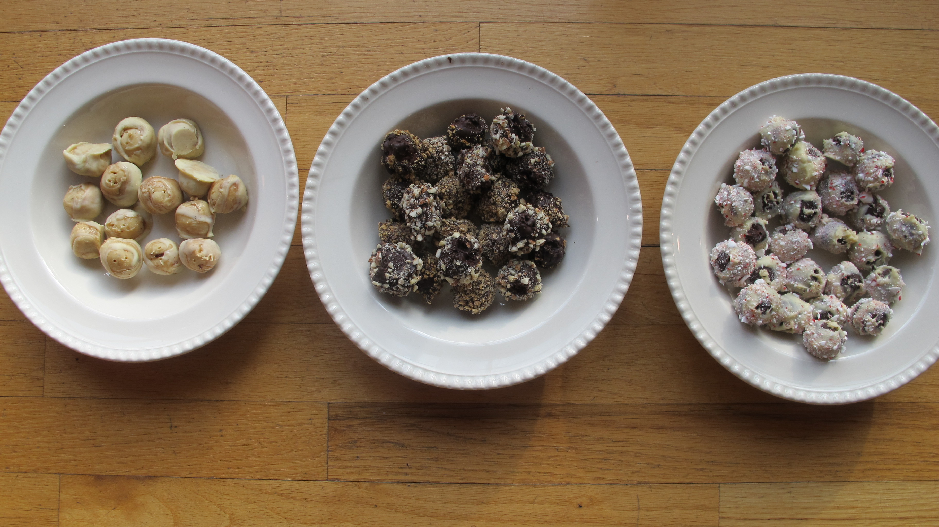 White Chocolate Truffles with Nonna's Cherry Jam, Dark Chocolate Hazelnut and Almond Truffles, and Peppermint Bark Truffles (from left to right).