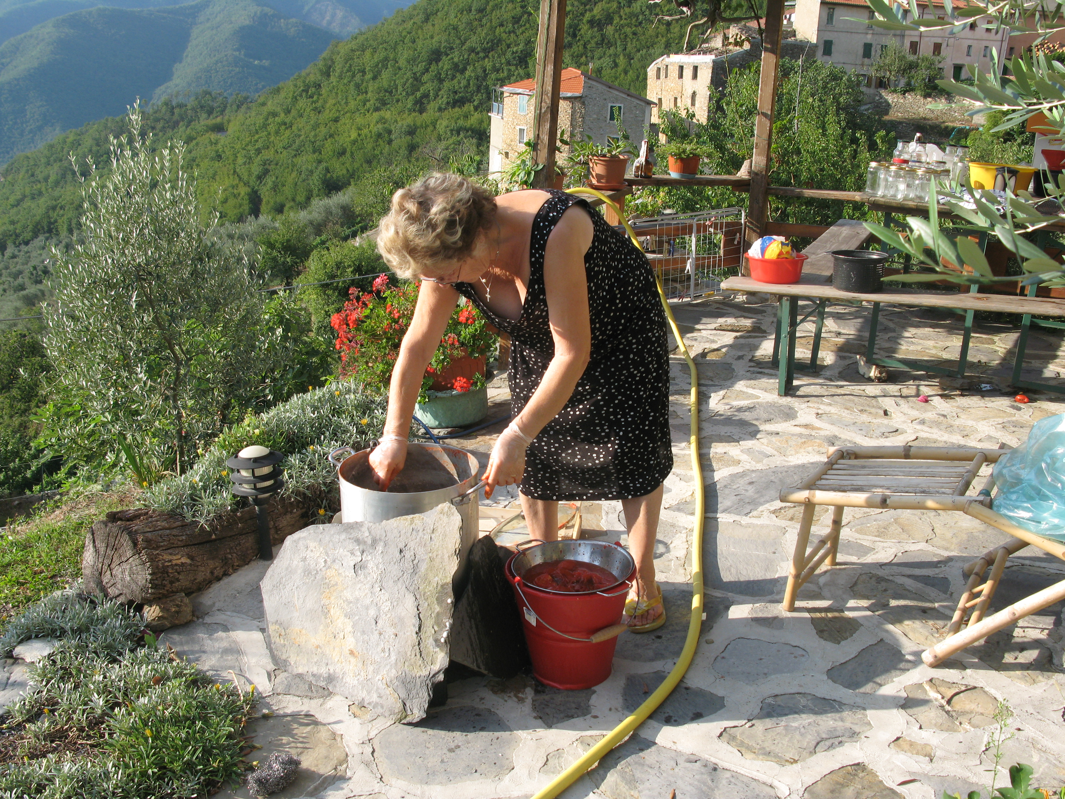 Nonna outside working on a batch of red sauce.