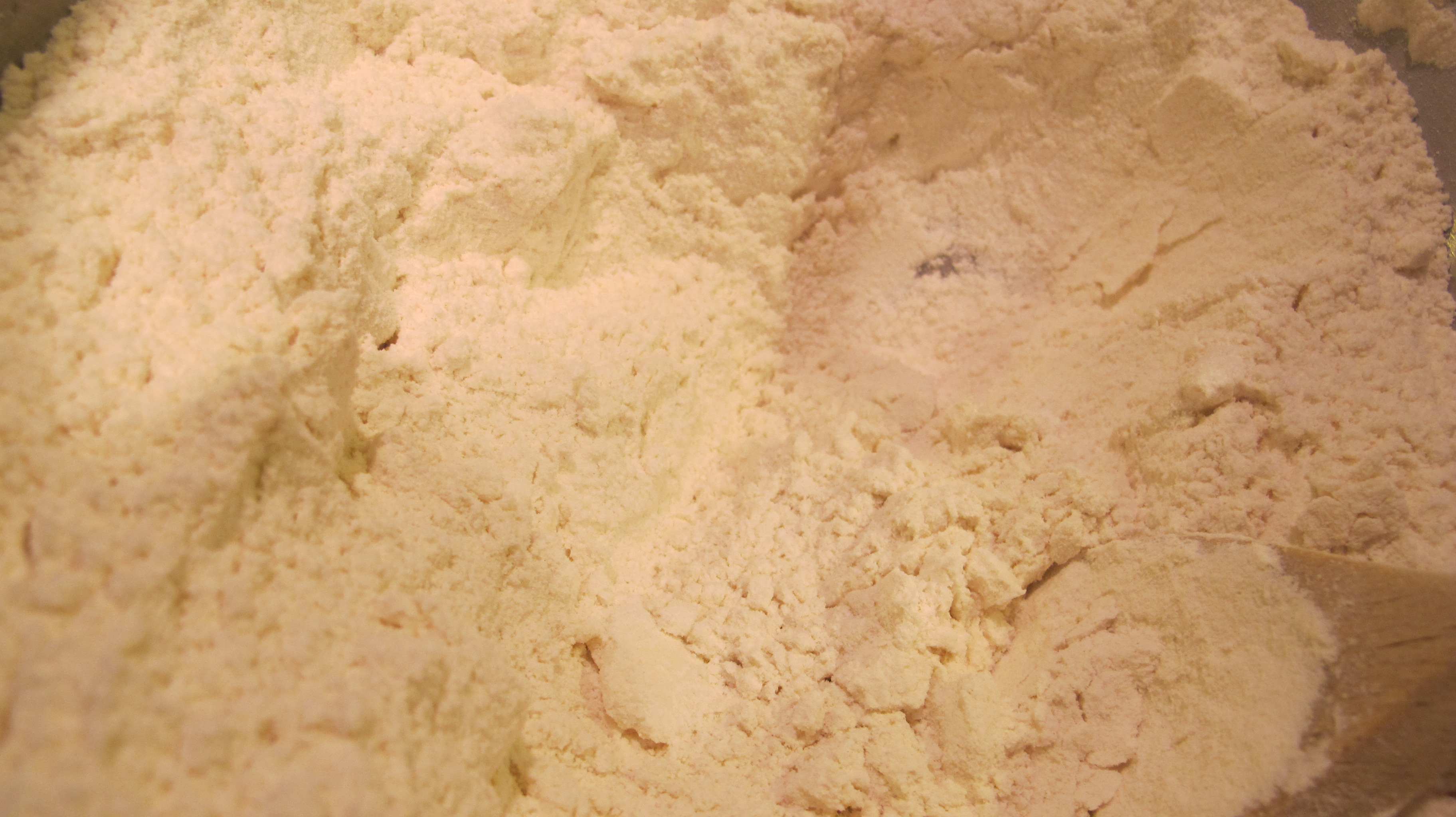 The dry mixture contains small crumbs from the butter.