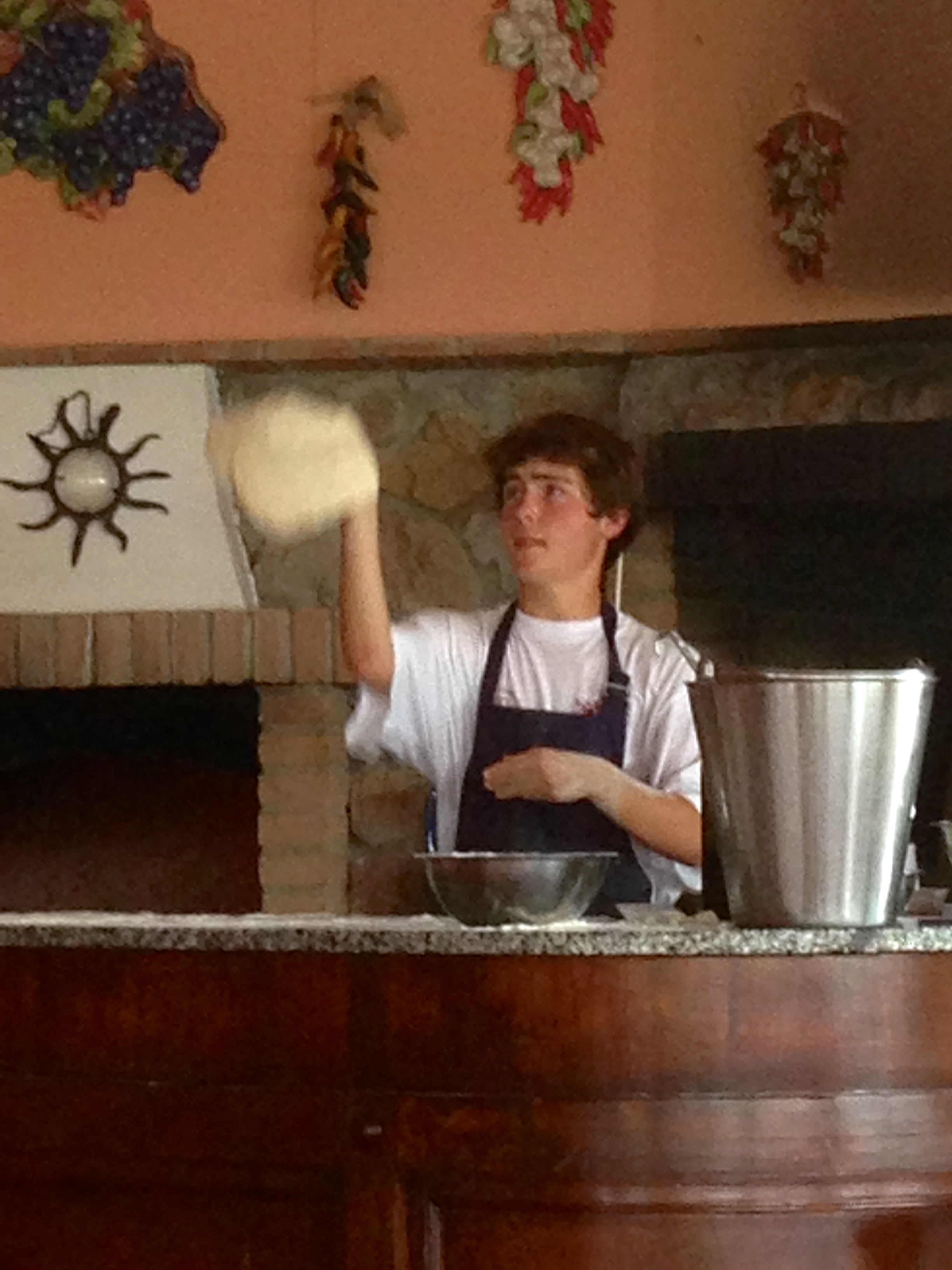 I confidently toss the dough in the air like a true pizzaiolo.