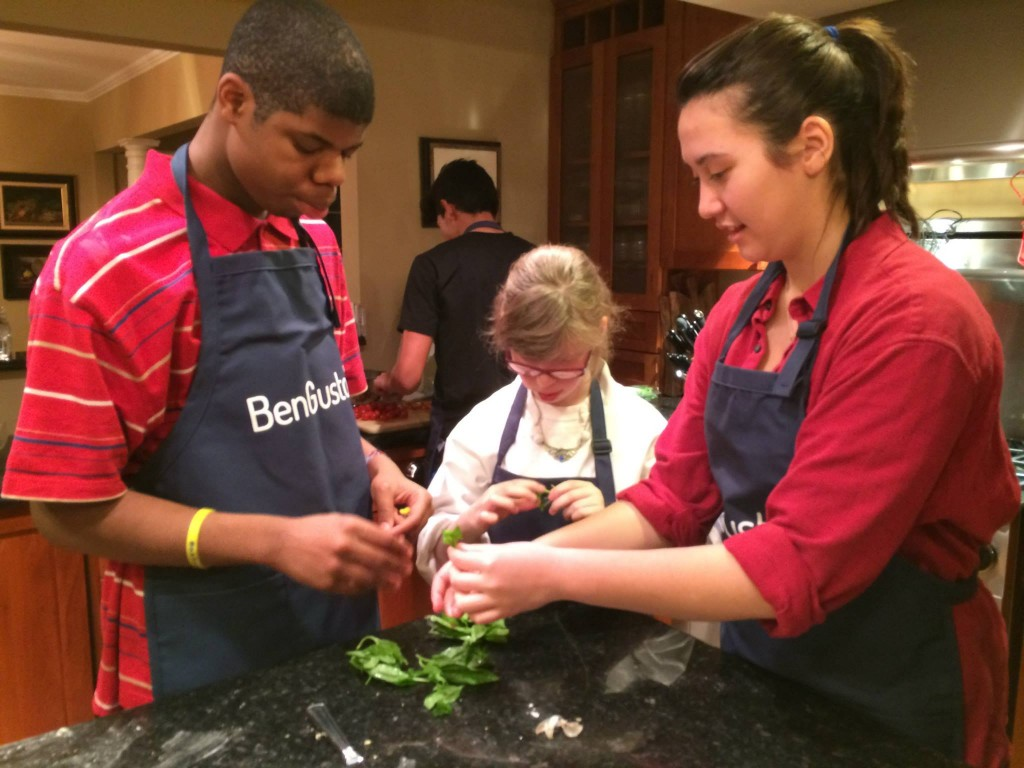 Angie (peer buddy), Marcus, and Halle pick the basil leaves.