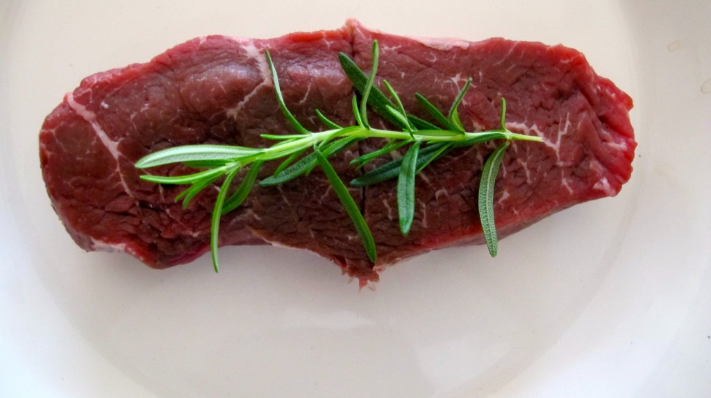 The beautiful color of a top sirloin steak with, one of our herbs of the day, rosemary.