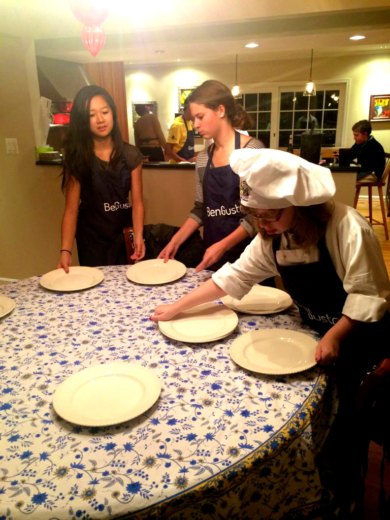 Chefs Halle, Kirsten, and Katie set the table for a post-lesson dinner.