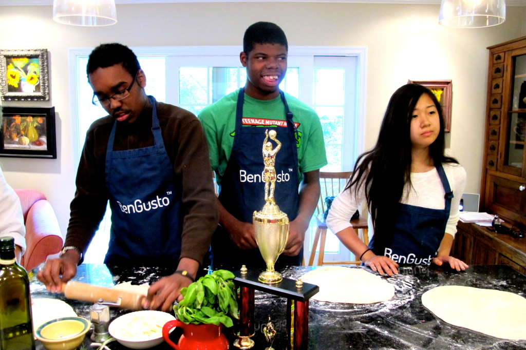 CJ, Marcus, and Katie. CJ rolls out his dough with a rolling pin.